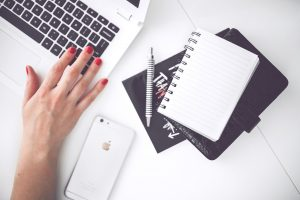 kaboompics-com_white-laptop-female-hand-note-pen-phone-desk